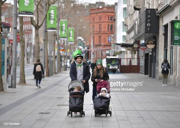 A couple walk their children along the normally bustling parade route on OConnell Street is quiet following the cancellation of the annual Saint...