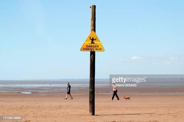 Couple walk their dog as they enjoy the warm weather on a beach in Weston-super-Mare, south west England on May 27 as lockdown measures are eased...