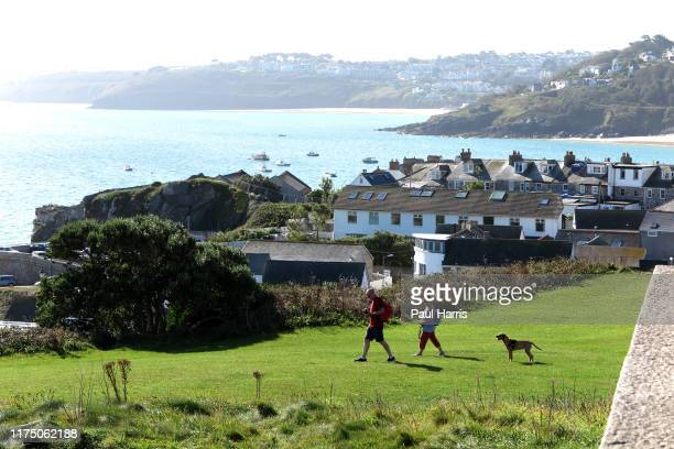 A couple walk their dog in front of St Nicholas Chapel St Ives during the 2019 September Summer Festival St Ives has become renowned for its number...