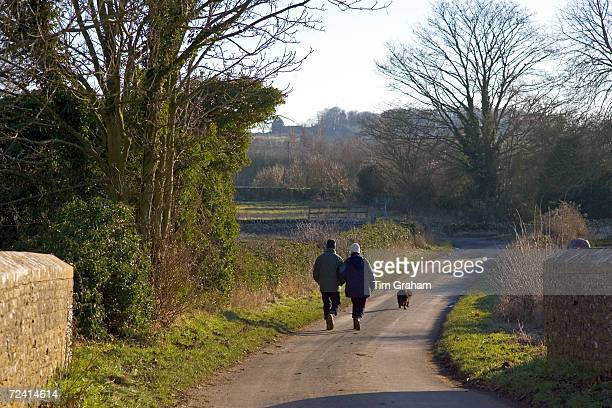 Couple walk their dog on a country lane in Asthall Leigh, Oxfordshire, United Kingdom.