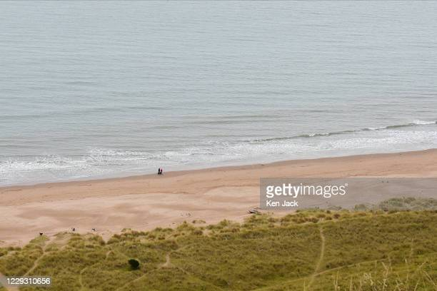 Couple walk their dog on the beach below the cliffs at St Cyrus National Nature Reserve on October 27, 2020 in St Cyrus, Scotland.