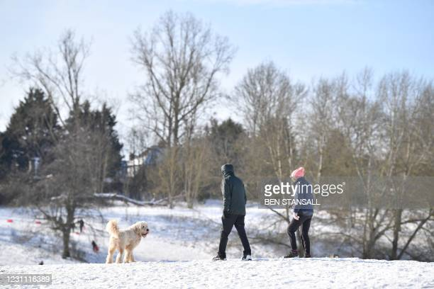 Couple walk their dog through Mote Park in Maidstone, southeast England on February 12, 2021 as snow blankets much of the country.