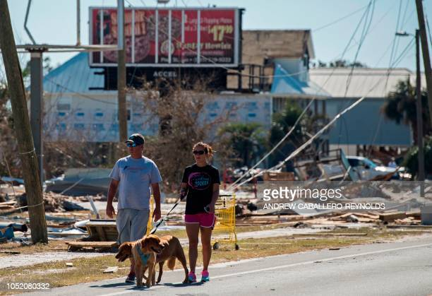 A couple walk their dogs down a street past destroyed buildings in Port St Joe beach Florida on October 13 three days after hurricane Michael hit the...