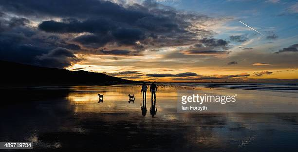 A couple walk their dogs on the beach as the sun sets on the Autumn Equinox which marks the first day of Autumn on September 23 2015 in Saltburn...