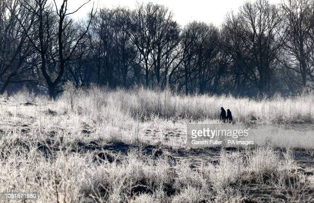 A couple walk through a frosty landscape near Ashford in Kent after the UK had its coldest night of the winter so far as the cold snap continues to...