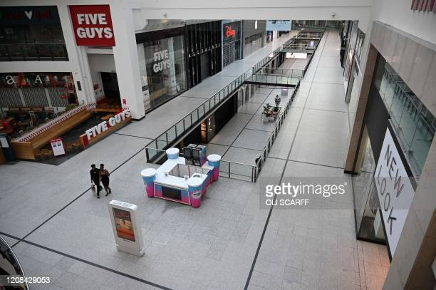 A couple walk through a neardeserted Arndale Centre in Manchester northwest England on March 27 2020 Manchester United will refund supporters if they...