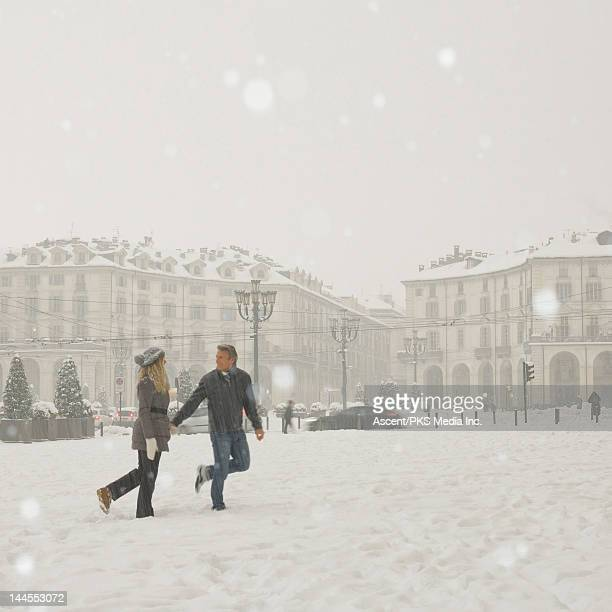 Couple walk through a snowstorm in a piazza