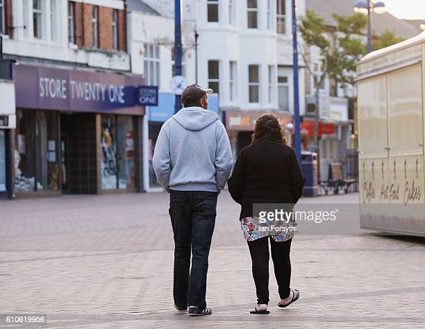 A couple walk through Redcar high street on September 27 2016 in Redcar United Kingdom One year on since the SSI steel making plant at Redcar was...