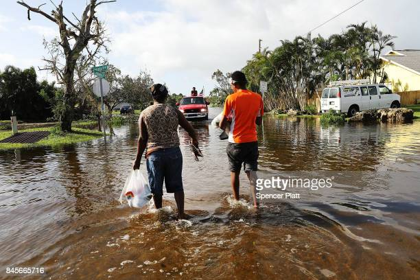 A couple walk through the flooded streets the morning after Hurricane Irma swept through the area on September 11 2017 in Naples Florida Hurricane...