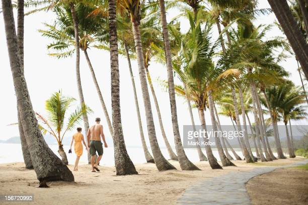A couple walk through the palm trees on the beach on November 13 2012 in Palm Cove Australia Located in Far North Queensland the Cairns region is one...