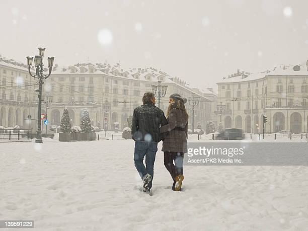 couple walk through urban piazza during snowstorm - turin stock pictures, royalty-free photos & images