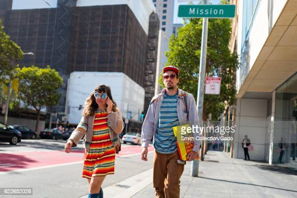 Couple walk together on the sidewalk along a city street, San Francisco, California, September 4, 2016. .