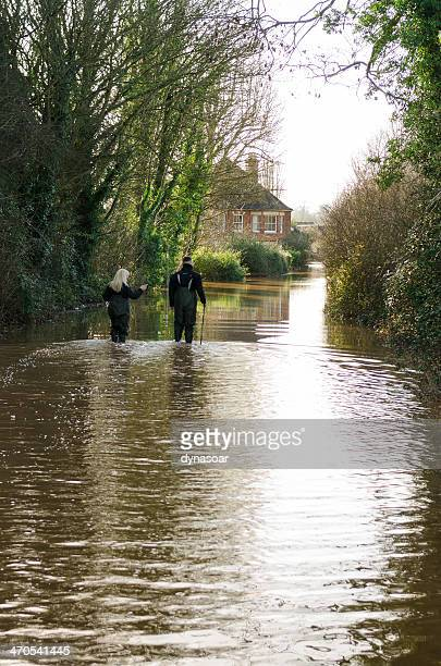 couple walk towards house down flooded road - extreme weather stock photos and pictures