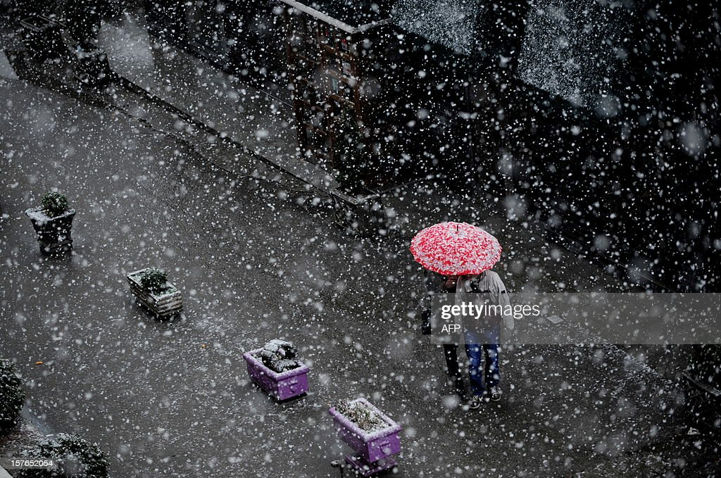 A couple walk under an umbrella during a heavy snowfall in Pristina on December 5, 2012.