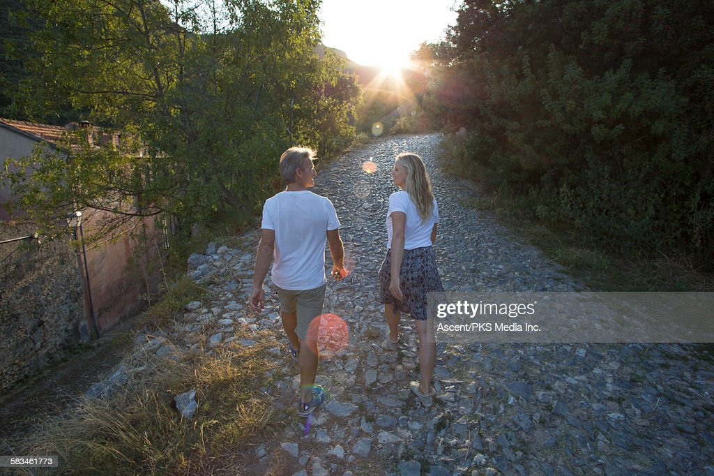 Couple walk up cobblestone path into sunrise : Stock Photo