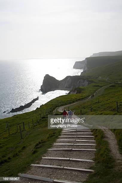 Couple walk up steps from Durdle Door Jurassic coast Dorset England
