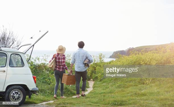 Couple walk with picnic hamper along coastal path to beach.
