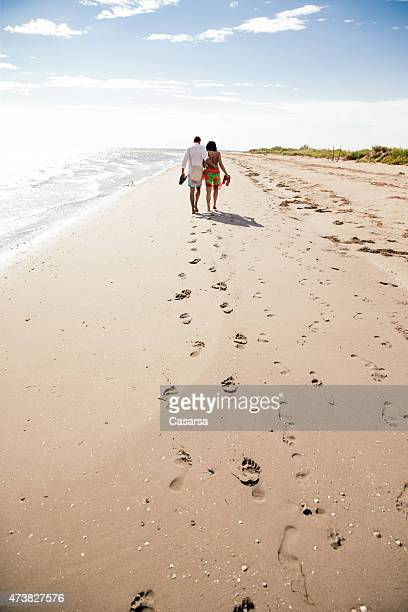 Couple walkind down the beach