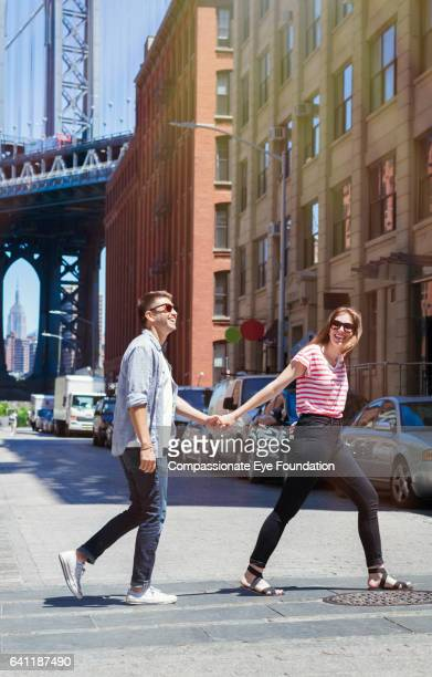 couple walking across city street hand in hand - street style new york stock pictures, royalty-free photos & images