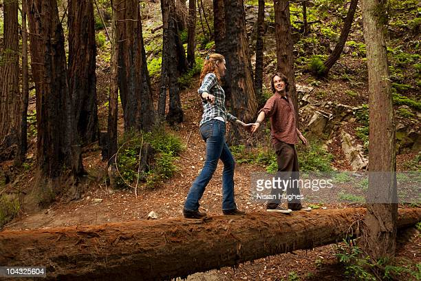 couple walking across fallen log - tree trunk stock pictures, royalty-free photos & images