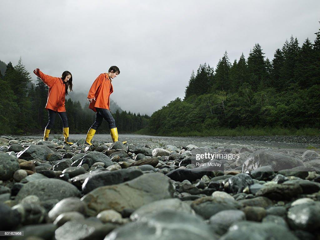 Couple walking across rocks of river bank. : Stock Photo