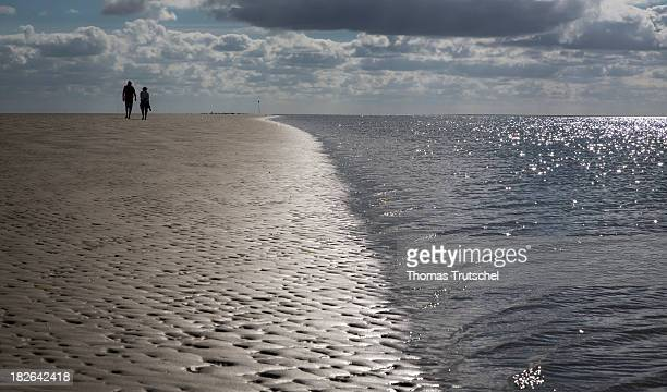 A couple walking across the mudflats of the island Fano