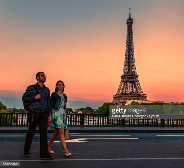 Couple Walking Against Eiffel Tower During Sunset