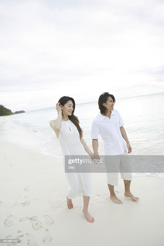 Couple Walking Along a Beach and Holding Hands : Stock Photo