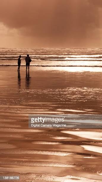 A couple walking along a beach during sunset taken on September 11 2008