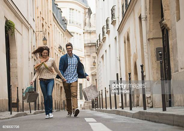 A couple walking along a narrow street in a historic city centre, with shopping bags.