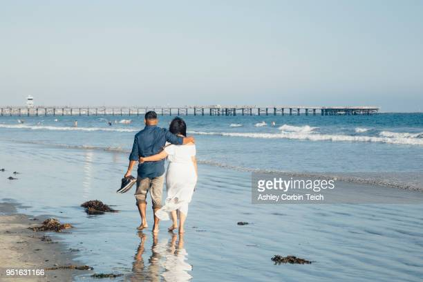 couple walking along beach, barefoot, rear view, seal beach, california, usa - seal beach stock pictures, royalty-free photos & images