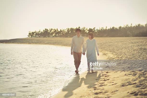 Couple walking along beach holding hands