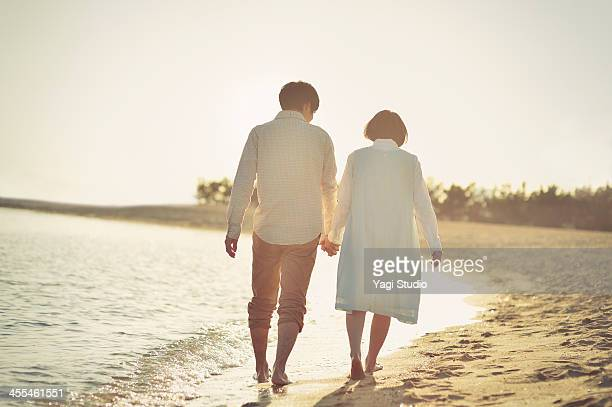 couple walking along beach holding hands - 愛 ストックフォトと画像