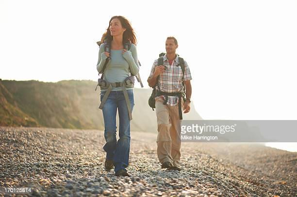 Couple walking along beach looking towards cliffs.