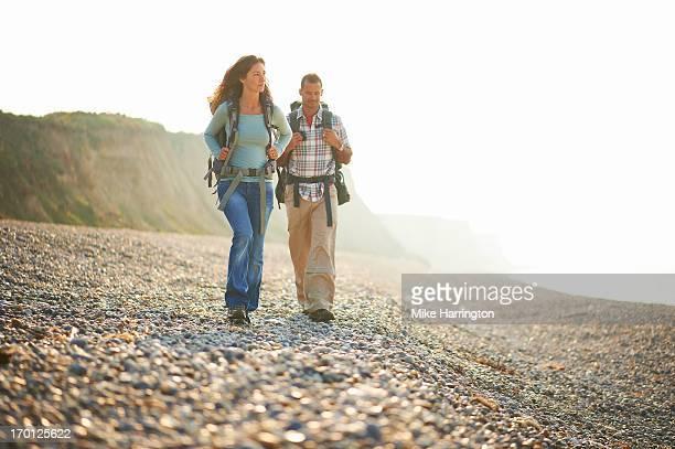 Couple walking along beach wearing rucksacks.