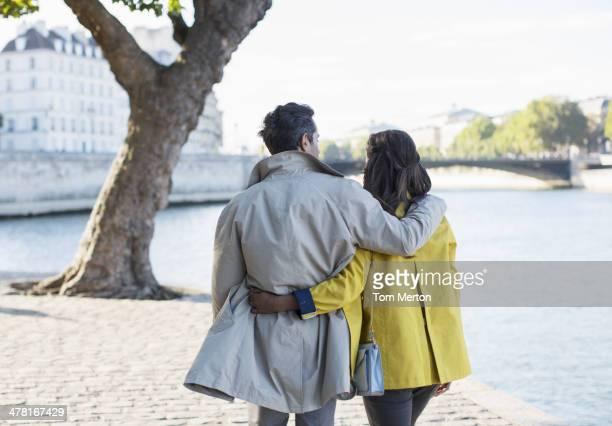 Couple walking along Seine River, Paris, France