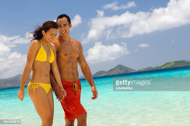 couple walking along the beach, holding hands and laughing