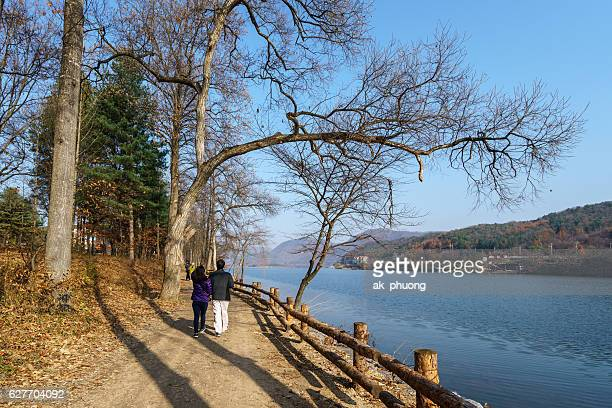 Couple walking along the trial with trees without leaf