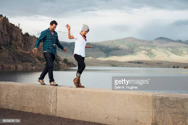 couple walking along wall beside dillon reservoir, silverthorne, colorado, usa - silverthorne stock photos and pictures