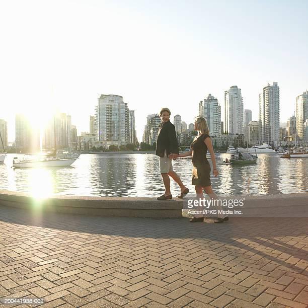 couple walking along waterfront, sunset (wide angle) - uferpromenade stock-fotos und bilder