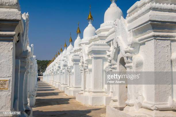 couple walking among the stupas in kuthodaw pagoda in mandalay, myanmar - peter adams stock pictures, royalty-free photos & images
