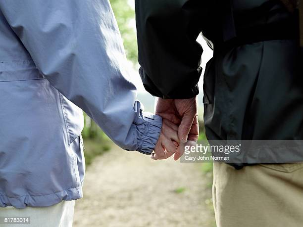 couple walking and holding hands  - king's lynn stock pictures, royalty-free photos & images