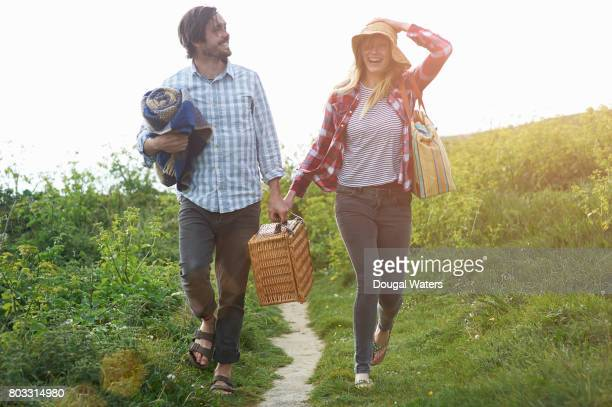 couple walking and laughing on coastal path with picnic hamper. - hamper stock pictures, royalty-free photos & images