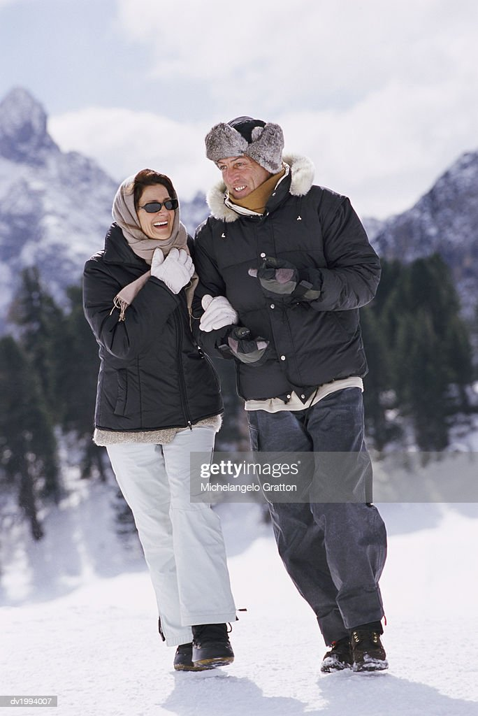 Couple Walking and Talking in Snow Covered Mountains : Stock Photo