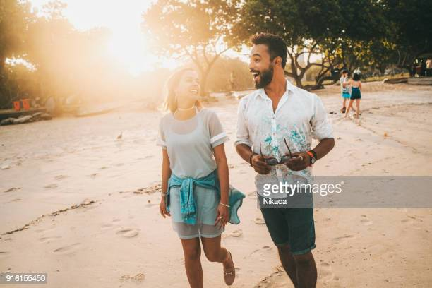 couple walking at beach during sunset
