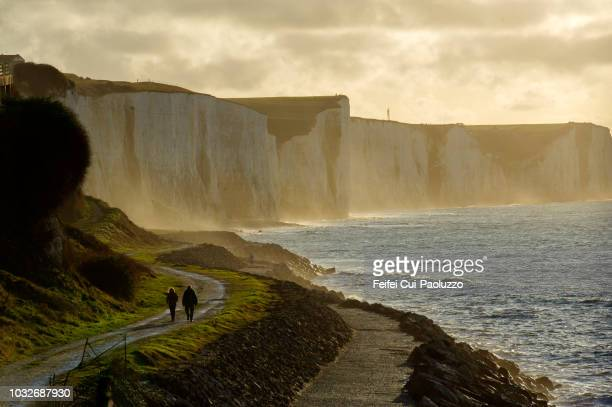 a couple walking at seaside of ault, somme, france - hauts de france stock photos and pictures