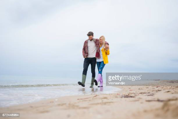 couple walking at the beach - yellow shoe stock photos and pictures