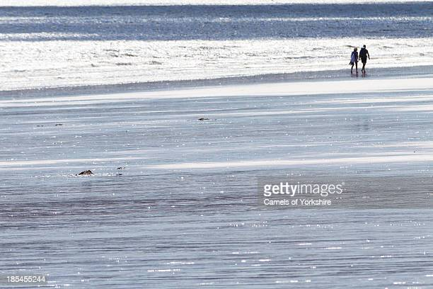 Couple walking at the sea edge on a sunny summer day with bright, shimmery reflections on the sand. Oxwich Bay, Gower Peninsula, South Wales, UK.