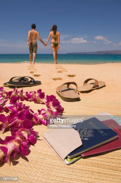 Couple walking away from passport and sandals on beach