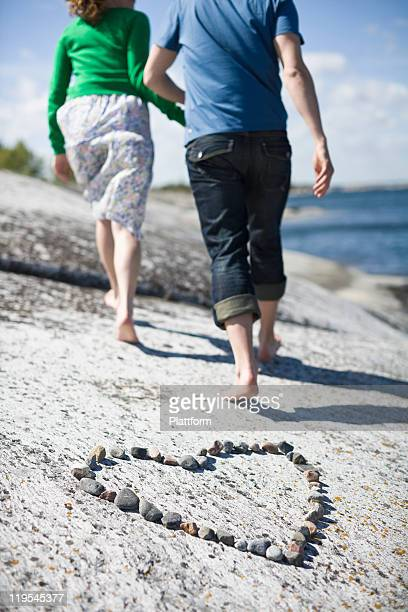 couple walking away from pebble heart at coast - close to stock pictures, royalty-free photos & images